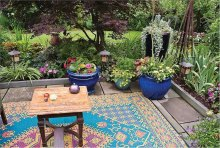 This gives you an idea of what you can do on your patio: flowers, pillows and rugs.