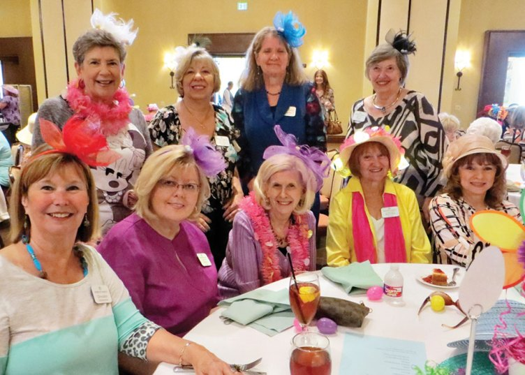 Women's Club members enjoying the April luncheon while wearing their fashionable fascinators and bonnets