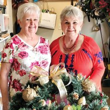 Sally Baggott and Jan Utzman creating the wreath centerpieces for the Hearts for Homes fundraiser event