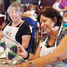 Dorothy Hogan looks on as Rosemary Simecek paints the finishing touch on her wine glass.