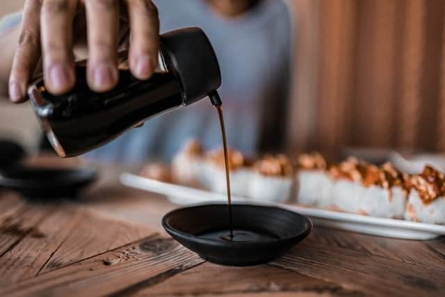pouring-soy-sauce-next-to-sushi-roll