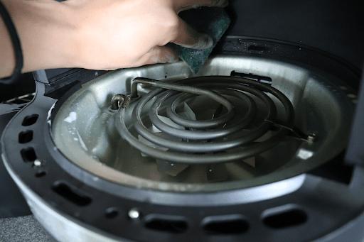 scrubbing-around-coil-of-air fryer