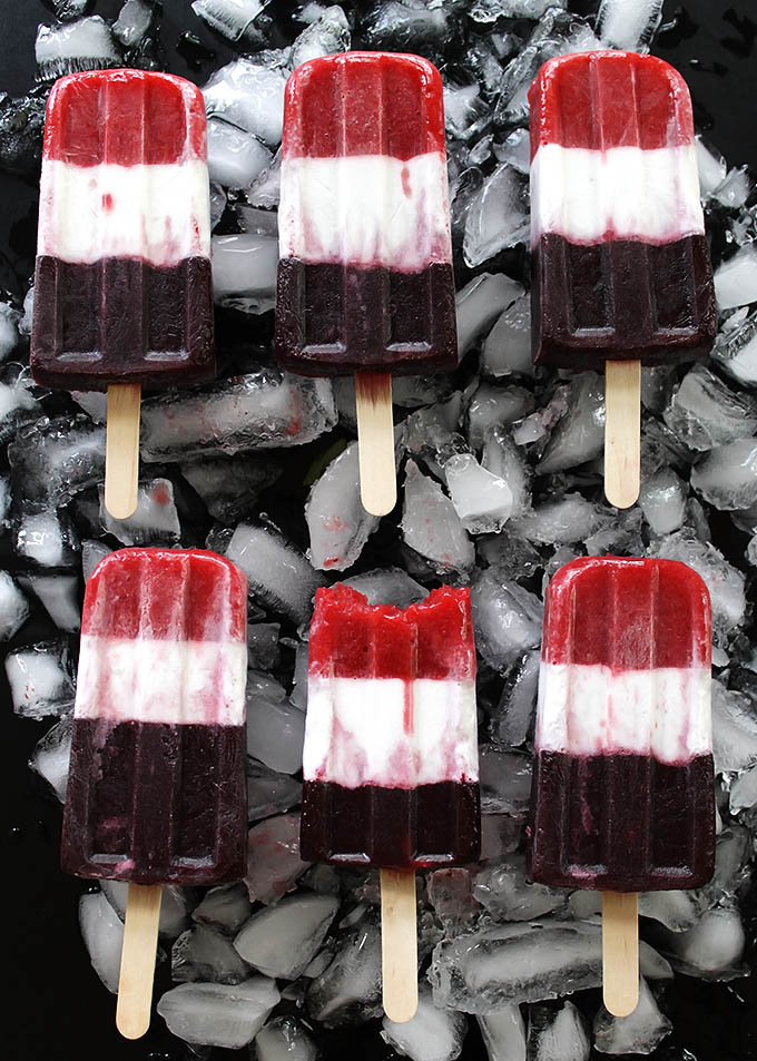 Vegan Red White and Blue Popsicles -Refreshing, EASY, healthy and festive 4th of July recipe. Pureed strawberries, coconut milk, and pureed blueberries make up the layers. Vegan/gluten free/ refined sugar free.