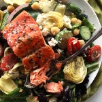 Easy Greek Salmon Salad - Fresh mixed greens loaded with Greek veggies. Tossed with a creamy Greek dressing and a hunk of pan seared salmon! This recipe comes together in just 25 minutes! Gluten Free.