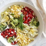 Summer Zucchini Noodle Salad with Creamy Basil Avocado Sauce - This salad is packed with fresh summertime veggies. Zucchini noodles are the base, they are tossed in a basil avocado sauce and that is all topped with fresh corn, grape tomatoes, artichoke hearts, and feta cheese. This recipe only takes 15 minutes to make! It is a great meal or a great side salad to any main dish or is filling enough as an entree . Vegan/vegetarian/gluten free | robustrecipes.com