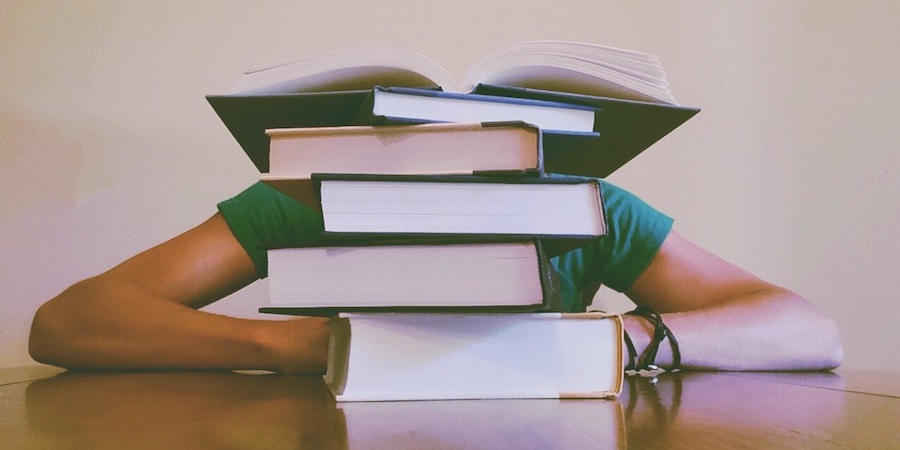 guy studying stack of books