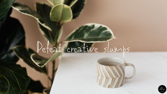 "Styled white table with a tan and white coffee mug sitting on it and a green leafy houseplant behind it. The text ""Defeat creative slump"" is overlaid on the image."