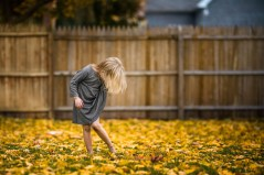 natural-light-environmental-portrait-of-little-girl-playing-in-golden-autumn-leaves-while-wearing-a-herringbone-fall-dress-by-sarah-wilkerson-1958