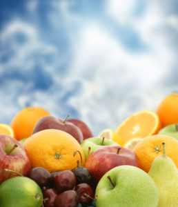 Large selection of fresh fruit against a blue sky background