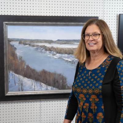 Artist standing in front of her art