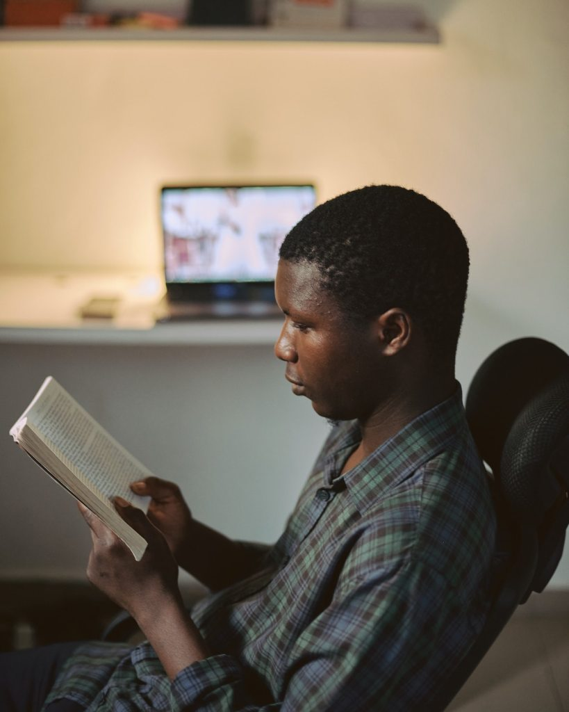 Closeup of a creative African man reading a bible with his workspace blurred in the background