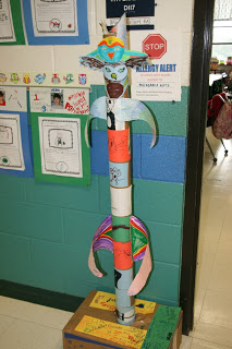 students decorate a large totem pole
