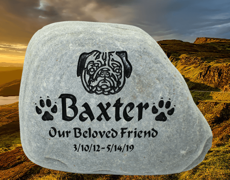 Example of Rock-It Creations engraved pet memorial stones. This one has the name Baxter, paw prints, and a pug face displayed on it.
