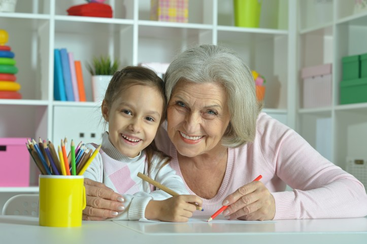 Grandmother with granddaughter drawing together