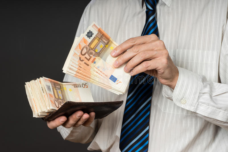 Le Meilleur Businessman Putting Banknotes In His Wallet Stack Of Ce Mois Ci