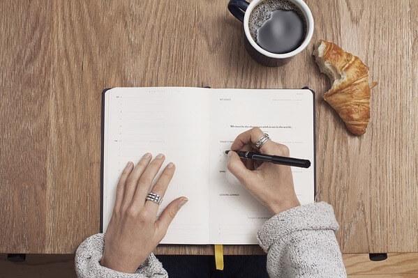 ノートに何か書いている女性