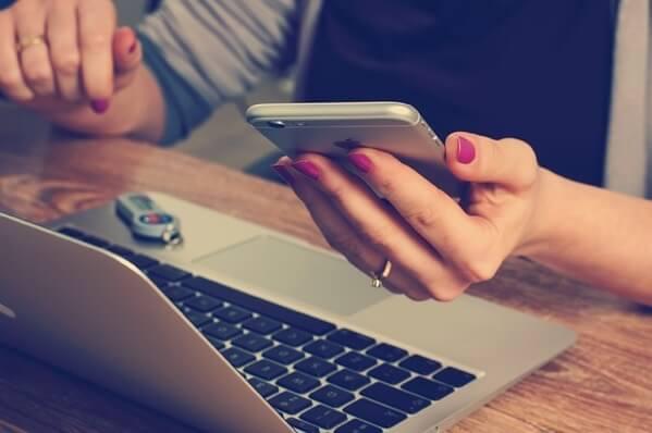 オフィスでMacBookとiPhoneを触っている人