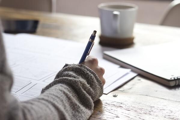 ノートに何かを書いている人