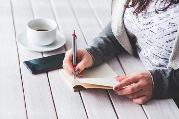 女性がノートに何かを書いている