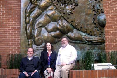 Giancarlo Ibárgüen S., rector, acompañado por Sherri y Rod Martin frente a Atlas Libertas.