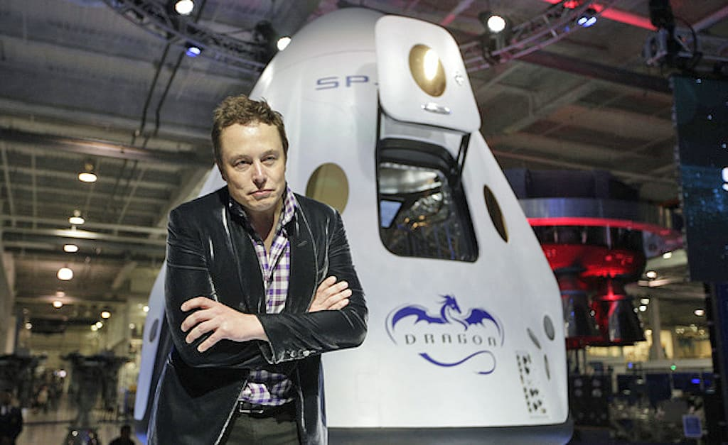 "FILE - In this Thursday, May 29, 2014 file photo, Elon Musk, CEO and CTO of SpaceX, listens to a question during a news conference in front of the SpaceX Dragon V2 spacecraft, designed to ferry astronauts to low-Earth orbit, at the headquarters in Hawthorne, Calif. The capsule was named for ""Puff the Magic Dragon,"" a jab at those who scoffed when Musk founded the company in 2002 and set the space bar exceedingly high. SpaceX went on to become the first private company to launch a spacecraft into orbit and return it safely to Earth in 2010. (AP Photo/Jae C. Hong)"