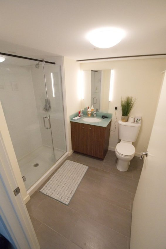 En-suite bath for platform bedroom, equipped with stall shower.