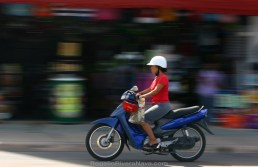 Woman riding a scooter motorcycle in a road in front of a souvenir store. Panning shot with background blurred. Cozumel island, Quintana Roo, México
