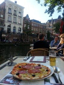 """Enjoying dinner in Utrecht. Although Amsterdam gets international chatter, my vote goes to Utrecht, another canal city just 30 minutes from Amsterdam by train. The architecture is a bit different. As you see from this picture, I'm sitting at a restaurant that is right next to the water; from what I saw, Amsterdam only has activity on the """"upper"""" level."""
