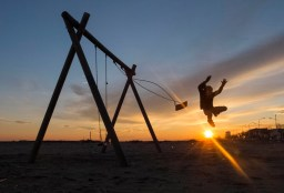 A boy jumps from a swing during sunset in Valras-Plage, southern France December 29, 2014. REUTERS/Yves Herman (FRANCE - Tags: ENVIRONMENT SOCIETY) ORG XMIT: YH01