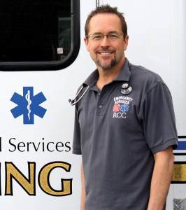 Gary Heigel EMS instructor at RCC posing in front of a training ambulance