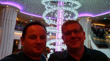 in the atrium of the Norwegian Epic, Nick and Greg of Roguetrippers, take a selfie in front of the elaborate chandelier.