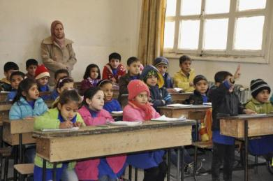 Kurdish students sit in their classroom in the town of Rumeilan