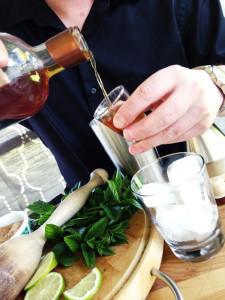 Pouring rum to create a mojito.