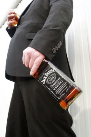 Man in a black suit sipping rokz Espresso Infused Jack Daniels whiskey.