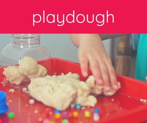 child's hand with playdough