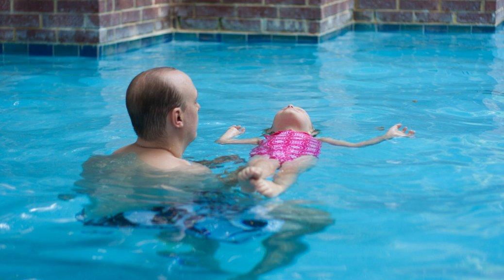 girl and dad in swimming pool