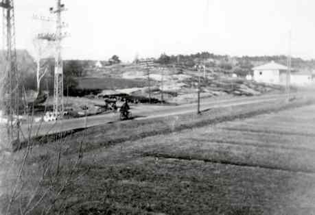 """Bildet fra ca 1950 er tatt der Råkollveien tar av til venstre fra RV 109. Den eneste trafikkant er en syklist. I 1910, i min mors barndom, satt barna her på Råfjellet og telte """"beisykler"""", på 50-tallet skrev barna bilnummer og i dag er antall biler det interessante. Foto: Sven Ørebæk"""