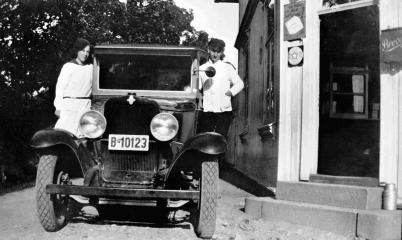 Sjåfør og varebil fra Fredrikstad brødbakeri ved den gamle inngangen til butikken. Jenta på stigbrettet er Lagertha Hassing