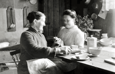 """Husfruen, som sitter til venstre, het Mathilde (f. 1847) og var som mannen svensk. Hun ble omtalt som Tilla, men oftest som Mor Jacobsen. """"Mor"""" var en hederstittel. Her er svigerdatteren Helga (f. Moum) på besøk med hekletøyet."""