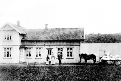Anton og Anna Henriksens landhandel, Soliveien 40. Rolf Henriksen bygde om huset i funkisstil etter at han overtok. På bildet står en butikkdame og ekteparet Anna og Anton Henriksen. Hestekaren er ukjent.