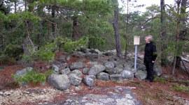Bilde 7: Bronsealdergrav med skilt og person. Her er gravhaugen utstyrt med skilt fra Fylkeskonservatoren. Foto: Lars Willy Corneliussen.