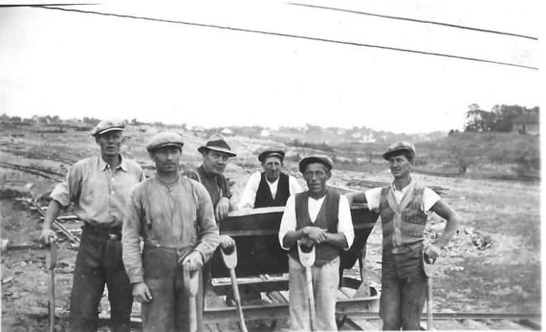 """Arbeiderne står rundt vaggen som transporterte lera frem til verket. Et ti-år tidligere ble lera trillet inn på trillebår. Men spaden var fortsatt nødvendig. Antagelig kom gravemaskinen i bruk så sent som på 1940-tallet. Vi ser fra venstre: 1. Erling fra Nøkleby, senere formann på """"Sultihjæl"""", 2. Rudolf Gundersen, Nøkleby, 3. Peder Johansen, Hauge, 4. Karl Martinsen, Lisleby, 5. ukjent og 6. Peder Pedersen, Omberg. I bakgrunnen Evje og Hauge-berget. På haugen til høyre lå huset til """"Møla-Alfred"""" Fotograf ukjent. Informanter til Birgit Holmen· Egil og Harry Huser, Arne Larsen, Oddvar Kristiansen (f. 1917), og Bjarne Engebretsen."""