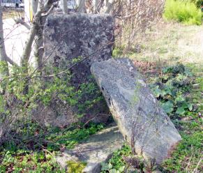 """På samme eiendom som Rådalsglasset ble funnet finnes ennå rester etter en stensetting, eller et gravminne, som Erling Johansen uttrykker det. I dag står bare en sten oppreist. En sten er forsvunnet, og en tredje ligger på bakken. Den ble i senere tid brakt dit fra Hauge hvor den angivelig skal ha gjort tjeneste som trapp. Erling Johansen tidfester minnet fra eldre jernalder. Trestenene lå i ytterkant av et stort gravfelt som strakk seg fra Saxegård sag til Fiolveien. Johansen antyder 20-25 graver. På 1920-tallet ble feltet ødelagt ved grusgraving. Massene ble brukt til havefyll og til Rolvsøyveien nedenfor. Aldersboligene på Grønlien ligger i dag trygt på gravfeltets grunn. Gravfeltet hørte antagelig til gården på Vestre Hauge. Funnet av glasset viser at bøndene på Hauge har """"sittet godt i det"""", hevder Johansen."""