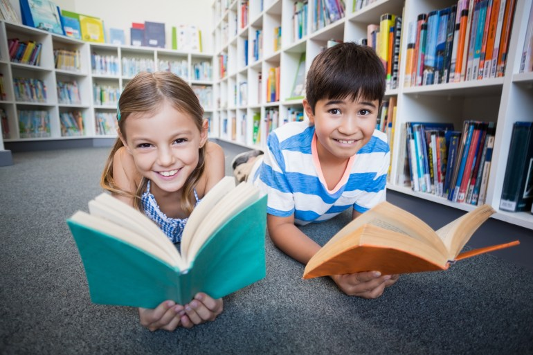 Happy school kids lying on floor and reading a book in library