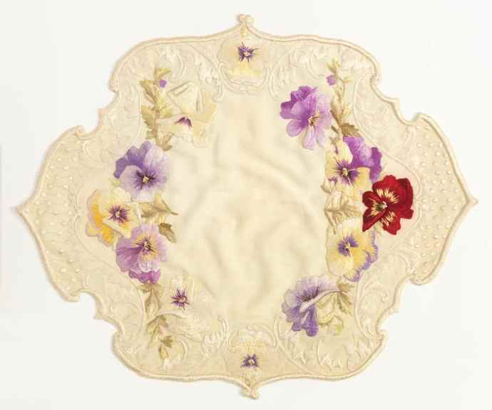 Embroidered table mat with a variety of colored pansies