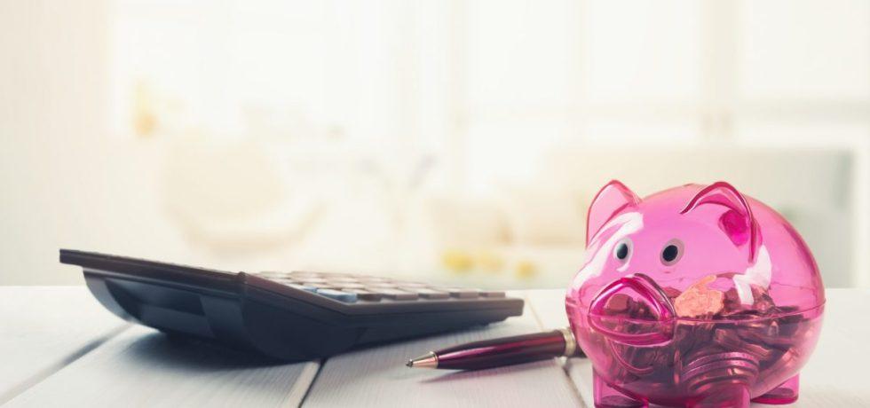 kalkulator, długopis i świnka skarbonka pomoga w przyotowaniu budzetu ślubu i wesela