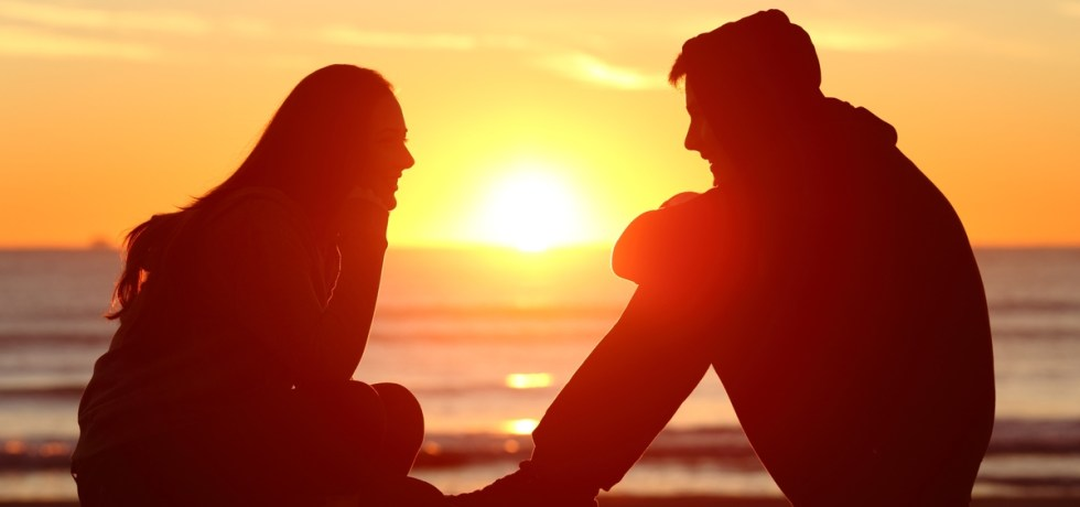 para rozmawiająca o uczuciach na tle romantycznego zachodzacego słońca