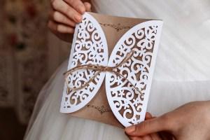 panna młoda trzymajaca eleganckie, rustykalne zaproszenie ślubne