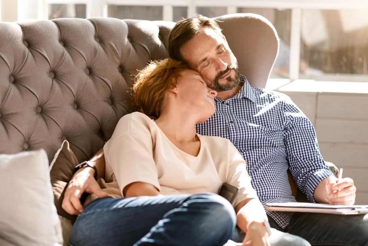 spokojna, zrelaksowana i szczęśliwa para przytulona do siebie na sofie