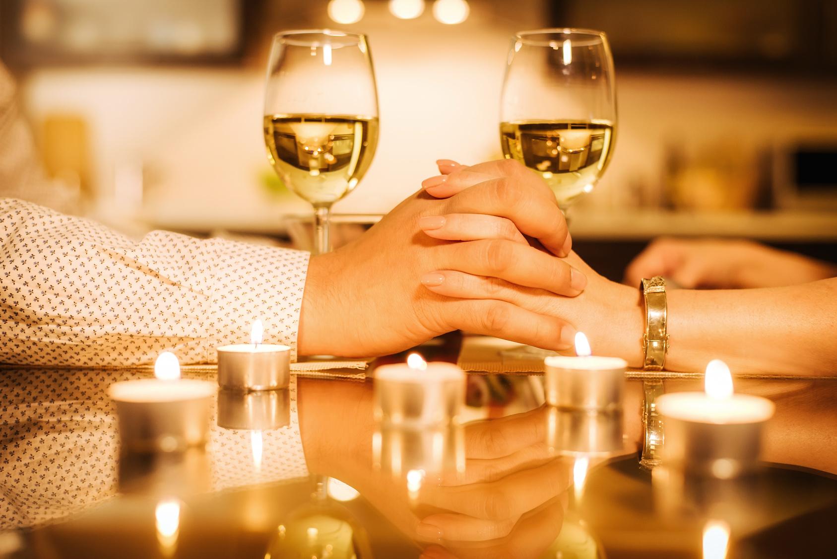 para pije wino i trzyma się za ręce podczas kolacji walntynkowej